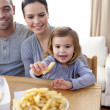 Little girl eating fries at home — Stock Photo