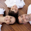 Stock Photo: Parents and kid lying on floor with heads together