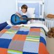 Little boy playing guitar in bedroom — Stock Photo