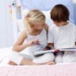 Brother and sister reading a book in bed — Stock Photo