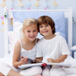Children reading a book in bedroom — Stock Photo