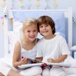 Foto Stock: Children reading a book in bedroom