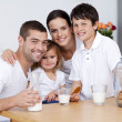 Happy family eating biscuits and drinking milk — Stock Photo #10299328