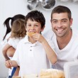 Father and son eating a toast in breakfast time — Stock Photo