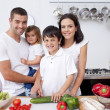 Son preparing food with his family - Stock Photo