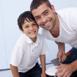 Smiling father and son painting a bedroom — Stock Photo #10299473