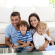 Portrait of happy family smiling in living-room — Stock Photo