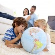 Royalty-Free Stock Photo: Children playing with a terrestrial globe in living-room