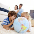 Children playing with a terrestrial globe in living-room — Stock Photo #10299581