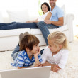 Friends using a laptop and couple on sofa - Stockfoto