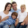 Smiling young family sitting on sofa — Stock Photo #10299636