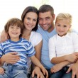 Happy family sitting on sofa at home — Stock Photo #10299645