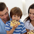 Happy boy eating pizza with ihs parents — Stock Photo
