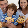 Portrait of family eating pizza on sofa - Stock Photo