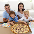 Stock Photo: Family eating pizzon sofa