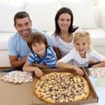 Family eating pizza on sofa — Stock Photo