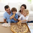Stock Photo: Young family eating pizzin living-room