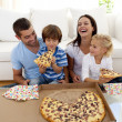 Parents and children eating pizza in living-room - Stock Photo