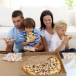 Family eating pizza in living-room - Stock Photo