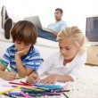 Children painting in living-room and father using a laptop — Stock Photo