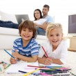 Smiling brother and sister painting in living-room — Stock Photo