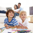 Children painting in living-room and parents on sofa — Stock Photo #10299754
