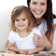 Smiling mother and daughter reading a book — Stock Photo #10299776