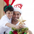 Stock Photo: Dad and boy decorating Christmas tree