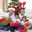 Foto Stock: Happy family celebrating Christmas at home