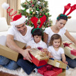 Happy family opening Christmas presents at home — ストック写真