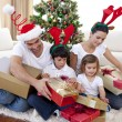 Foto Stock: Happy family opening Christmas presents at home