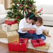 Happy brother and sister opening Christmas gifts — Stock Photo