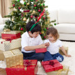 Happy brother and sister looking at Christmas gifts — Stock Photo