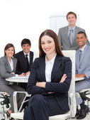 Smiling businesswoman sitting in front of her team — Stock Photo