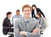Assertive male executive with folded arms sitting in front of hi — Stock Photo