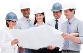 Multi-ethnic group of architects wearing hardhats — Stock Photo