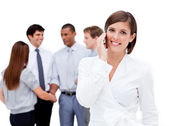 Attractive businesswoman on phone in front of her team — Стоковое фото