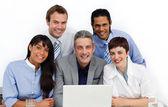Bir dizüstü bilgisayar kullanarak çok etnik gruptan oluşan iş grubu — Stok fotoğraf