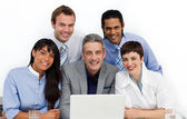 Multi-ethnic business group using a laptop — Stock fotografie