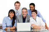Smiling business group using a laptop — Stock Photo