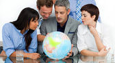 International business looking at a terrestrial globe — Stock Photo