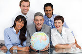 Confident business partners holding a globe — Stock Photo