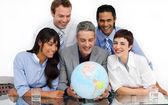 Een zakelijke groep weergegeven: diversiteit kijken naar een aardse glob — Stockfoto
