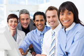 Multi-ethnic smiling business team sitting in a row — Stock Photo