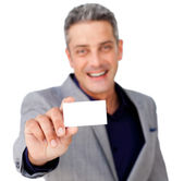 Smiling confident businessman holding a white card — Stock Photo