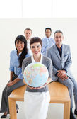 Multi-ethnic business holding a terrestrial globe — Stock Photo