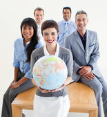 Cheerful multi-ethnic business holding a terrestrial glob — Stok fotoğraf