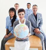 Vrolijke multi-etnische zaken houden een aardse glob — Stockfoto