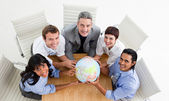 Lachende bedrijf houden een globe — Stockfoto
