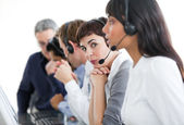 Charming businesswoman with headset on in a call center — Stock Photo